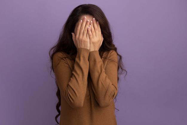 Молодая красивая девушка в коричневом свитере с высоким воротом закрыла лицо руками, изолированными на фиолетовой стене