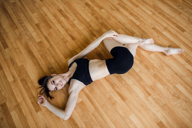 Young beautiful girl wearing fashion sports wear doing exercise on mat at loft gym, top view. high quality photo