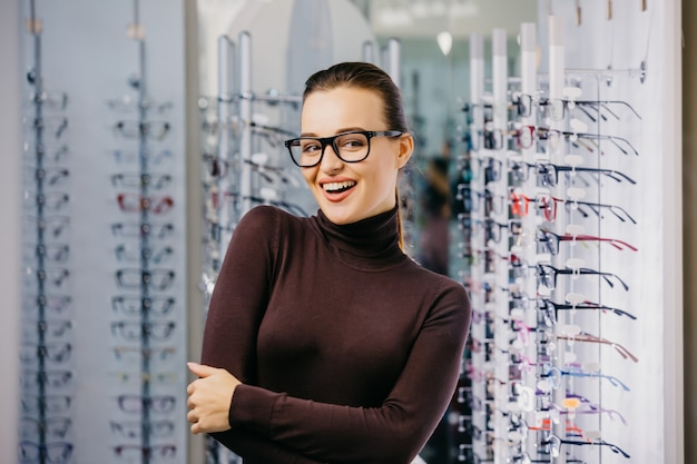 Young beautiful girl wearing glasses smiling near the stand