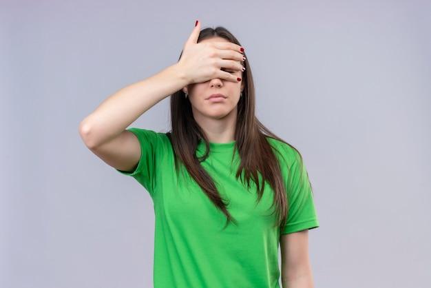 Молодая красивая девушка в зеленой футболке закрывает глаза рукой, глядя сквозь пальцы, стоя на изолированном белом фоне
