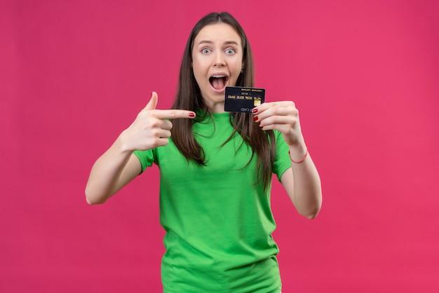 緑のtシャツを着て美しい少女が終了し、孤立したピンクの背景の上に立ってそれを指で指している幸せなクレジットカードを保持