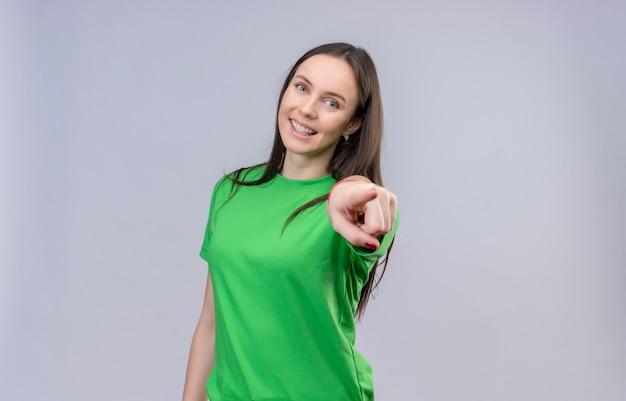 Молодая красивая девушка в зеленой футболке счастлива и позитивно улыбается, весело указывая на камеру, стоящую на изолированном белом фоне