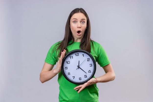 孤立した白い背景の上に驚いて驚いて立っている探している時計を保持している緑のtシャツを着て美しい少女
