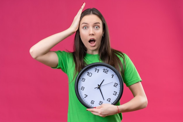 Young beautiful girl wearing green t-shirt holding clock looking amazed and surprised touching head with hand standing over isolated pink background