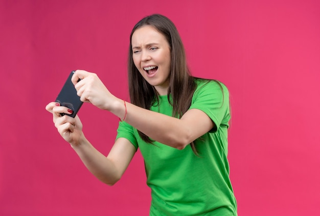 Young beautiful girl wearing green t-shirt holding smartphone looking at it stressed and nervous standing over isolated pink background