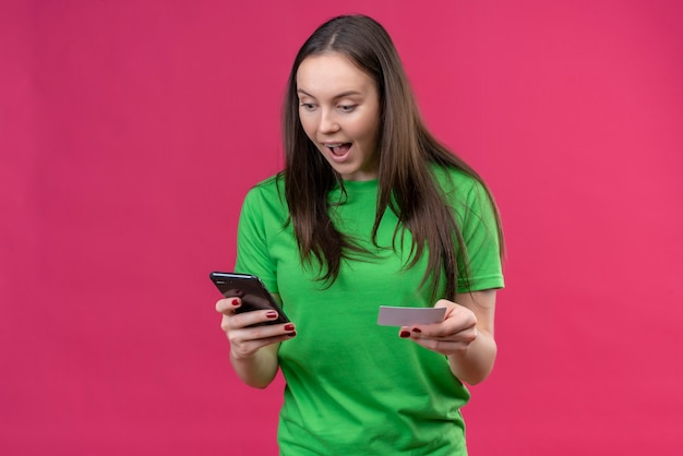 Young beautiful girl wearing green t-shirt holding smartphone looking at screen amazed and surprised standing over isolated pink background