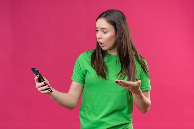 Giovane bella ragazza che indossa la maglietta verde che tiene smartphone guardando lo schermo confuso e molto ansioso in piedi su sfondo rosa isolato