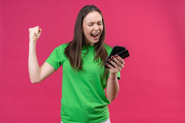 Giovane bella ragazza che indossa la t-shirt verde tenendo lo smartphone guardando lo schermo uscito e felice innalzamento pugno chiuso sorridendo allegramente gioendo il suo successo in piedi su rosa isolato bac