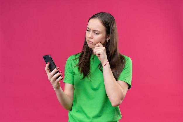 Giovane bella ragazza che indossa la maglietta verde che tiene smartphone guardando lo schermo con espressione pensierosa sul viso in piedi su sfondo rosa isolato