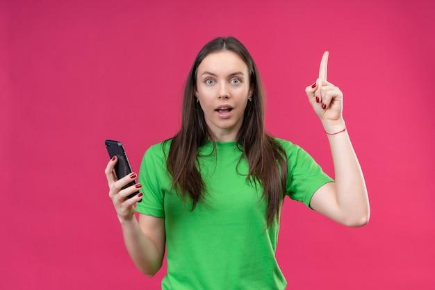 고립 된 분홍색 배경 위에 새로운 아이디어 개념 서있는 데 스마트 폰 가리키는 손가락을 들고 녹색 티셔츠를 입고 젊은 아름 다운 소녀
