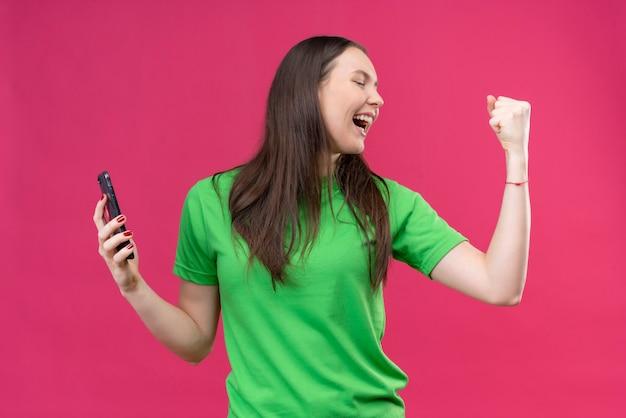 孤立したピンクの背景の上に立って彼女の成功を喜んで拳クレイジー幸せを上げるスマートフォンを保持している緑のtシャツを着ている美しい少女