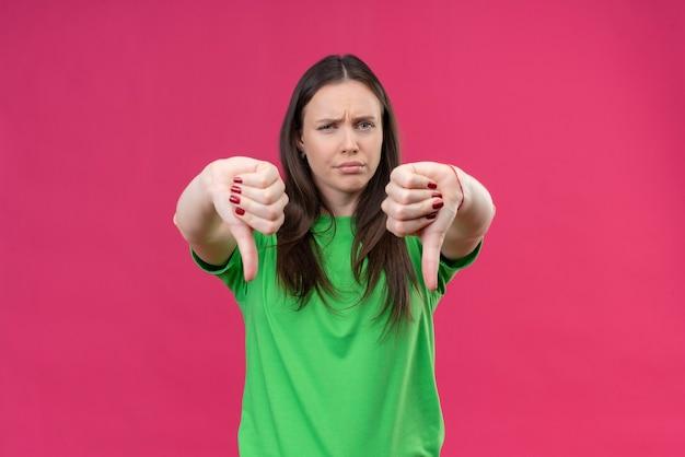 Молодая красивая девушка в зеленой футболке выглядит недовольной с нахмуренным лицом, показывая большие пальцы вниз, стоя на изолированном розовом фоне