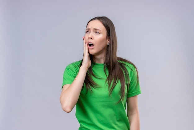 Young beautiful girl wearing green t-shirt looking unwell touching her cheek suffering from toothache standing over isolated white background