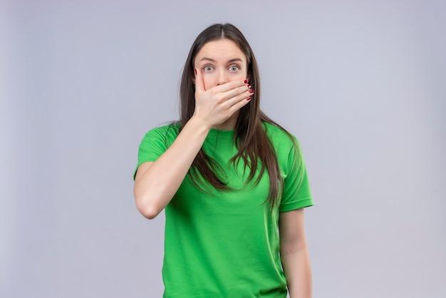 緑のtシャツを着ている美しい少女ショック分離の白い背景の上に立っている手で口を覆っています