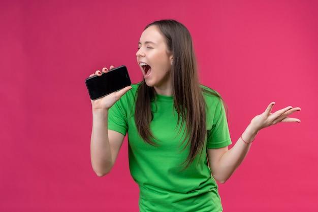Молодая красивая девушка в зеленой футболке кричит на свой смартфон, используя в качестве микрофона, стоя на изолированном розовом фоне