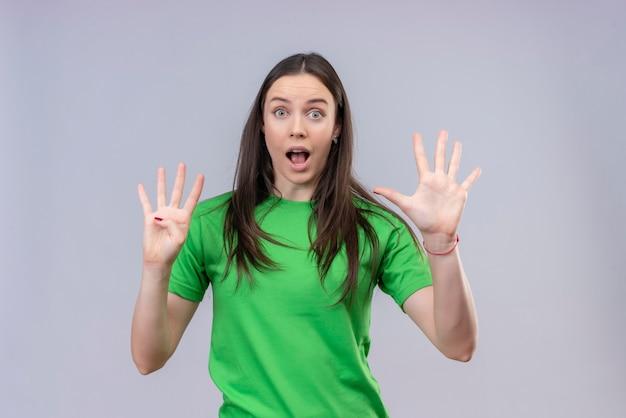 Молодая красивая девушка в зеленой футболке показывает пальцами номер четыре и смотрит вверх с удивлением, стоя на изолированном белом фоне
