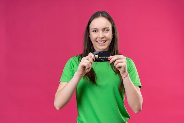 Молодая красивая девушка в зеленой футболке показывает кредитную карту со счастливым лицом, улыбаясь, стоя на изолированном розовом фоне
