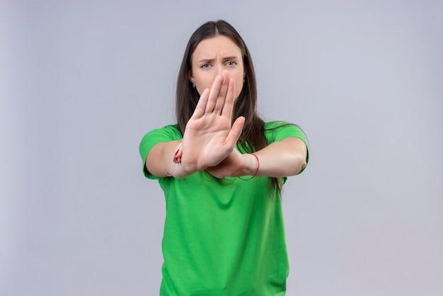 孤立した白い背景の上に立って不快なカメラを見て一時停止の標識を作る開いた手で立っている緑のtシャツを着て美しい少女