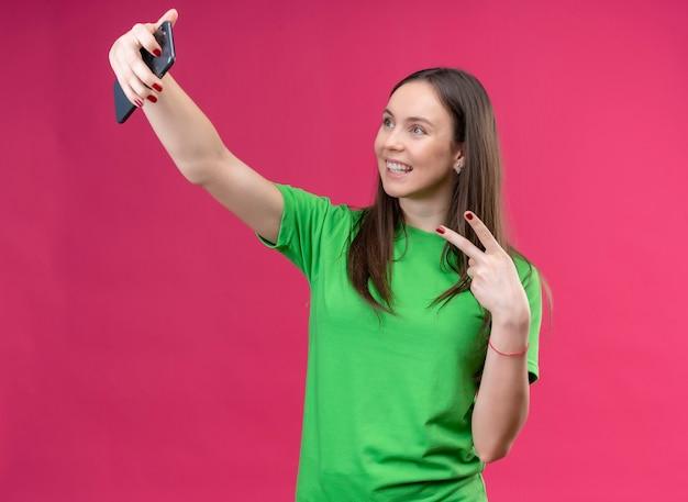 Молодая красивая девушка в зеленой футболке делает селфи с помощью смартфона, показывая знак победы, весело улыбаясь, стоя на изолированном розовом фоне
