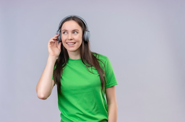 Молодая красивая девушка в зеленой футболке с наушниками, наслаждаясь любимой музыкой, весело улыбаясь, стоя на изолированном белом фоне