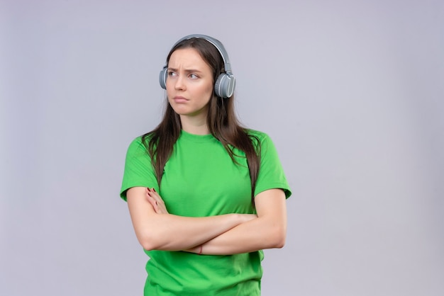 Young beautiful girl wearing green t-shirt with headphones standing with arms crossed looking aside displeased over isolated white background