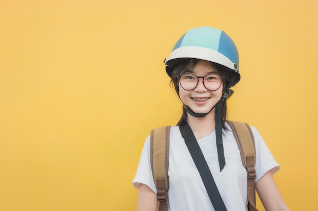 Young beautiful girl wearing a helmet on yellow background