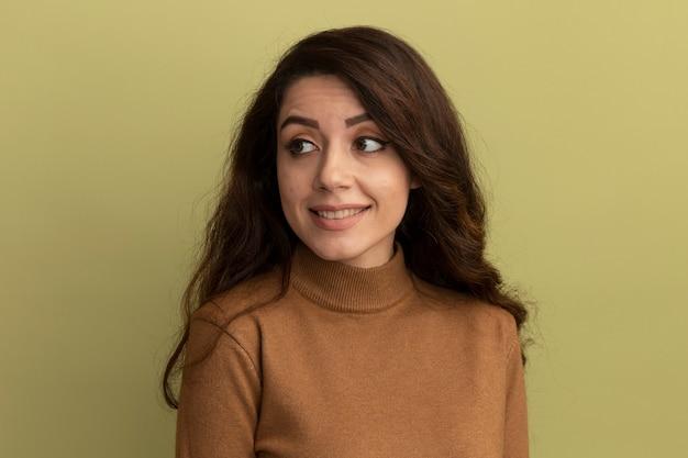 Giovane bella ragazza che indossa una maglietta verde oliva - isolata sulla parete rosa