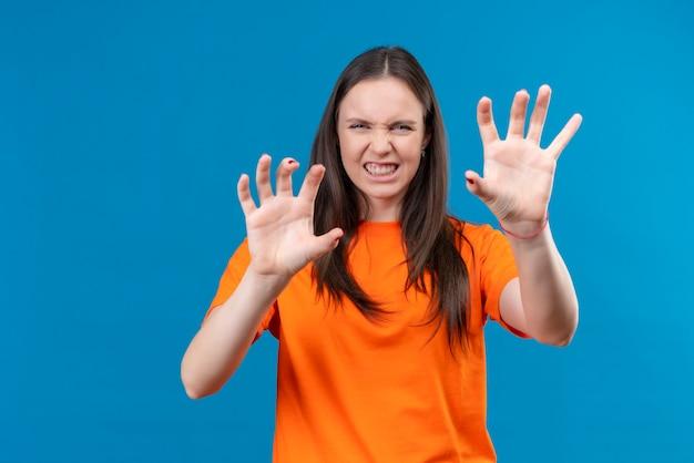 Молодая красивая девушка в оранжевой футболке рычит, как животное, делая жест кошачьих когтей, стоя на изолированном синем фоне