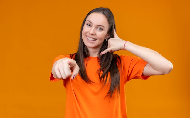 Young beautiful girl wearing orange t-shirt happy and positive smiling pointing to camera making call me gesture standing over isolated orange background