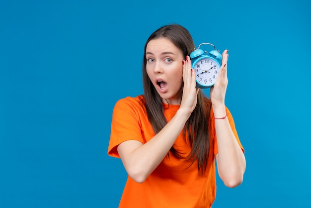 Young beautiful girl wearing orange t-shirt holding alarm clock looking amazed and surprised standing over isolated blue background