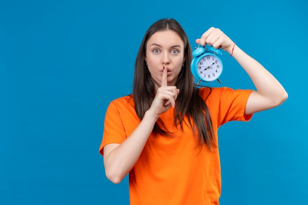 Young beautiful girl wearing orange t-shirt holding alarm clock making silence gesture with finger on lips standing over isolated blue background