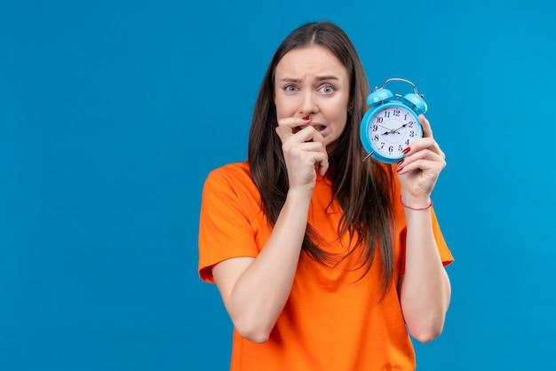 目覚まし時計を保持しているオレンジ色のtシャツを着ている美しい少女が強調し、孤立した青い背景の上に立っている彼女の爪を噛んで緊張