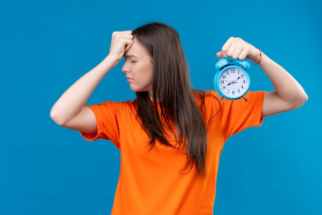 Young beautiful girl wearing orange t-shirt holding alarm clock touching her head for mistake bad memory concept standing over  isolated blue background