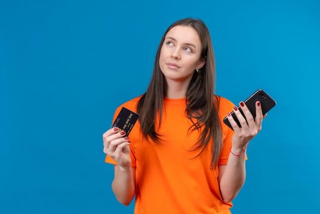 고립 된 파란색 배경 위에 서있는 선택을 시도 잠겨있는 표정으로 찾고 생각에 잠겨있는 표정으로 찾고 스마트 폰 및 신용 카드를 들고 오렌지 티셔츠를 입고 젊은 아름 다운 소녀