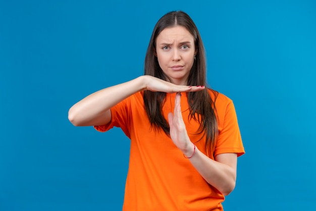 孤立した青い背景の上に立ってタイムアウトジェスチャーを作る手で不機嫌なジェスチャーを探しているオレンジ色のtシャツを着ている美しい少女