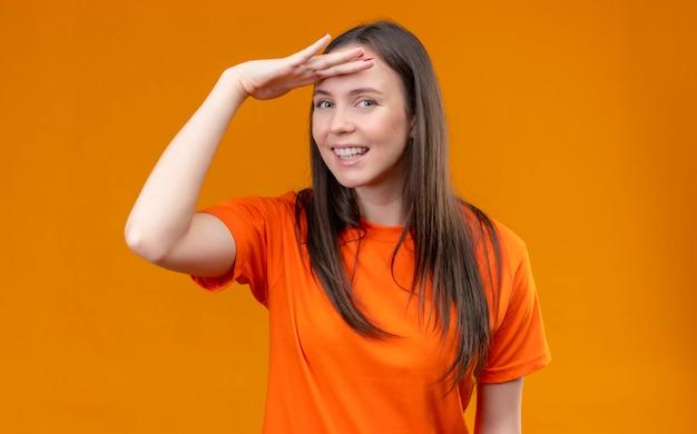 Молодая красивая девушка в оранжевой футболке смотрит вдаль с рукой над головой, чтобы посмотреть, как кто-то улыбается, стоя на изолированном оранжевом фоне