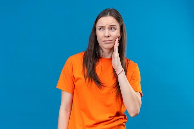 고립 된 파란색 배경 위에 서있는 그녀의 뺨 느낌 치통을 만지고 몸이 불편 찾고 오렌지 티셔츠를 입고 젊은 아름 다운 소녀