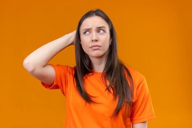 孤立したオレンジ色の背景の上に立って顔に物思いにふける不審な表情で脇をよそ見をオレンジ色のtシャツを着ている美しい少女