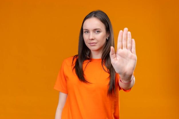 Молодая красивая девушка в оранжевой футболке стоит с открытой рукой, делая жест стоп, стоя на изолированном оранжевом фоне
