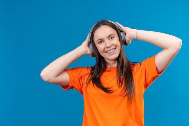 Молодая красивая девушка в оранжевой футболке с наушниками, наслаждаясь своей любимой музыкой, улыбаясь счастливым и позитивным положением на изолированном синем фоне