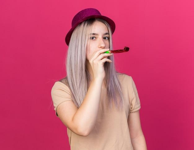 Giovane bella ragazza che indossa cappello da festa che soffia fischio di festa isolato su parete rosa