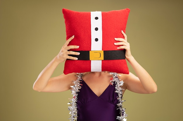 Giovane bella ragazza che indossa un abito viola e corona con ghirlanda sul collo coperto il viso con cuscino natalizio isolato sulla parete verde oliva