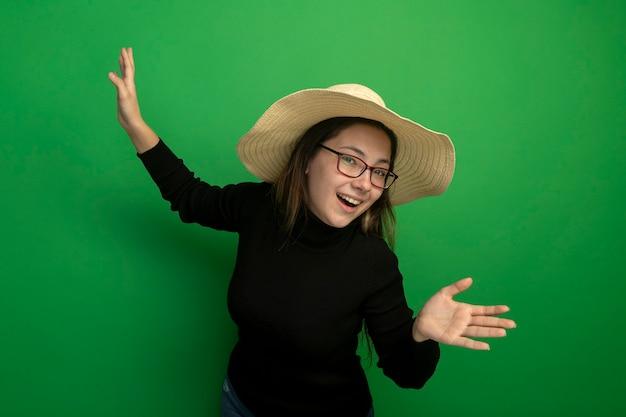 Молодая красивая девушка в летней шляпе в черной водолазке и очках делает приветственный жест руками