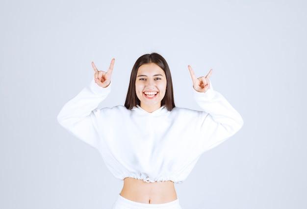 手を上げてロックシンボルをやって白いtシャツを着て若い美しい少女。