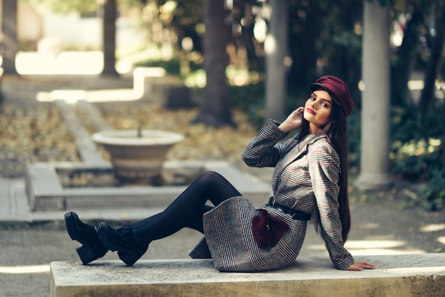 Young beautiful girl wearing winter coat and cap sitting on a bench in urban park.