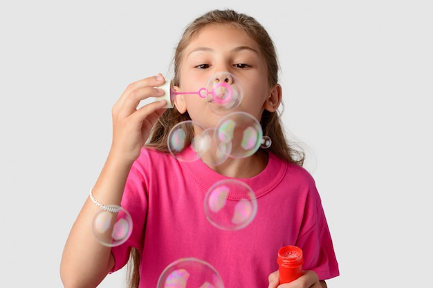 Young beautiful girl wears pink t-shirt blowing soap bubbles against a grey background