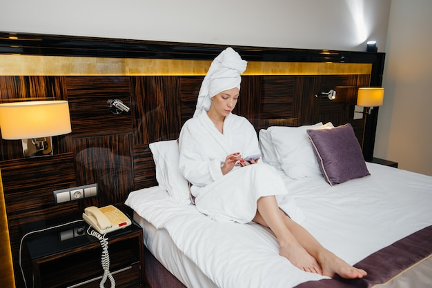 A young beautiful girl in a white coat is talking on the phone in her hotel room.