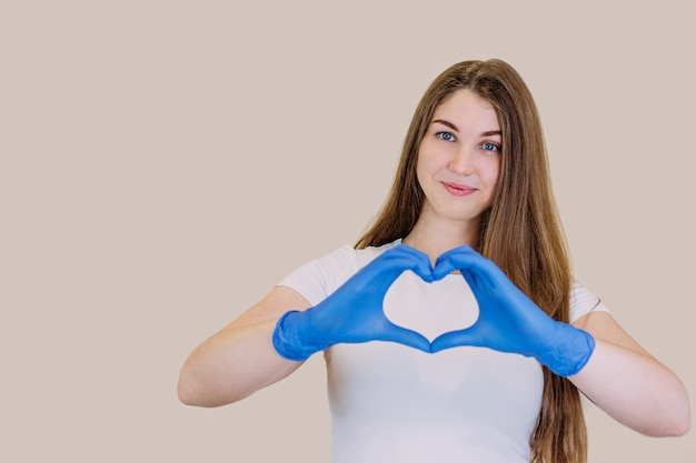 Young beautiful girl in a white t-shirt in blue gloves holding hands in the shape of a heart