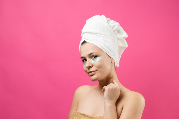 Young beautiful girl in a white towel on his head wears collagen gel patches under her eyes