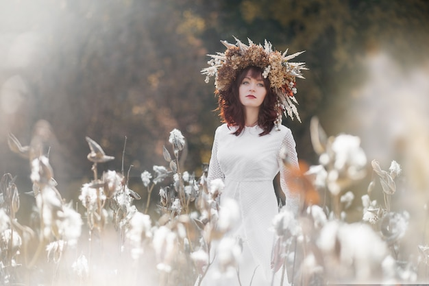 Young beautiful girl in a white vintage dress and wreath of dried flowers on the head in a autumn field